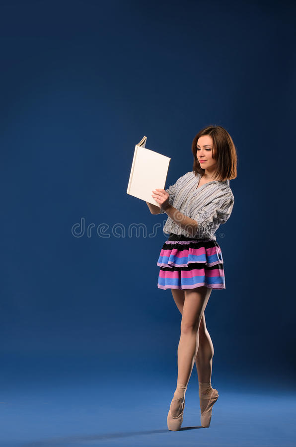 Female dancer on tiptoe reading book stock photography