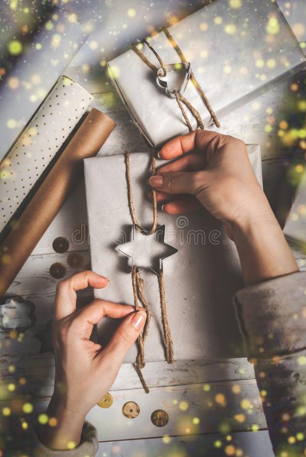 Female decorating Christmas presents gift box. Collection in vintage, rustic, diy style. For Christmas or New Year concept royalty free stock images