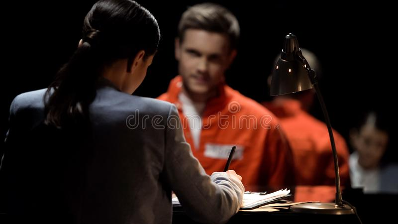 Female defense attorney writing accused prisoners statements for court, advocacy. Stock photo royalty free stock photos