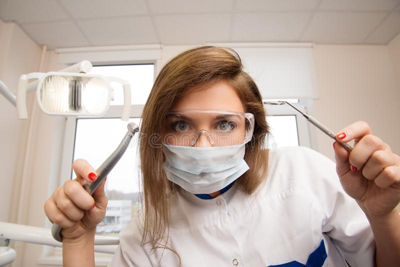 Female dentist with dental tools stock photography