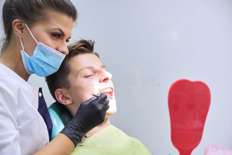Female dentist doctor treats teeth to teenage boy stock photography
