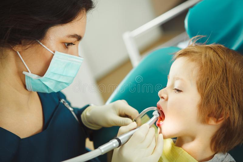 Female dentist drills the teeth of small child. Prevention of tooth decay. stock images