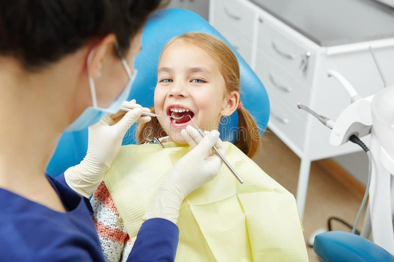 Female dentist examines of smiling child at the pediatric dentistry clinic. Happy little girl royalty free stock photo