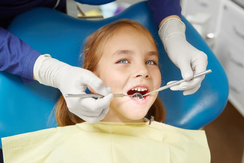Female dentist examines of smiling child at the pediatric dentistry clinic. Happy little girl stock images