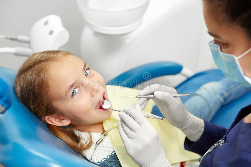 Female dentist examining little girl teeth in pediatric dentistry clinic. Early prevention, raising awareness, oral hygiene demonstration concept royalty free stock photo