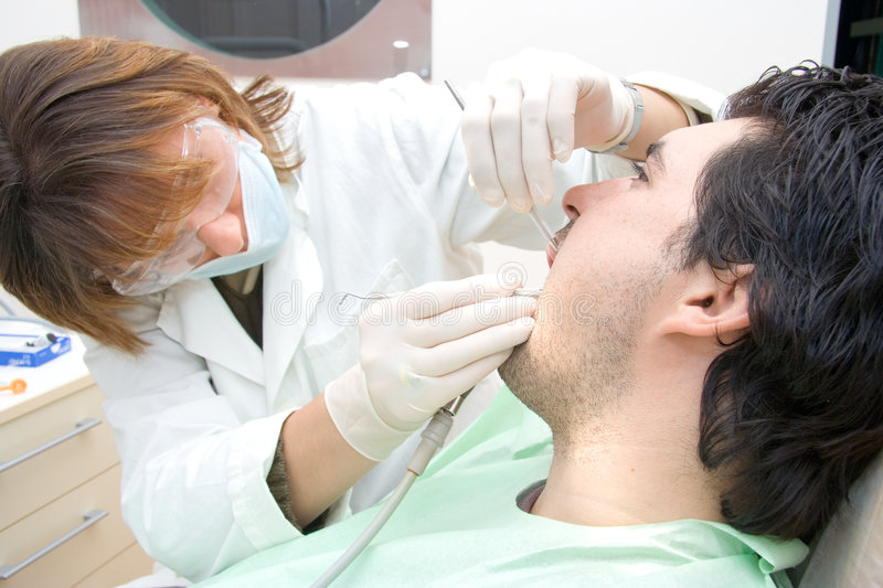 Female dentist examining a patient royalty free stock photography