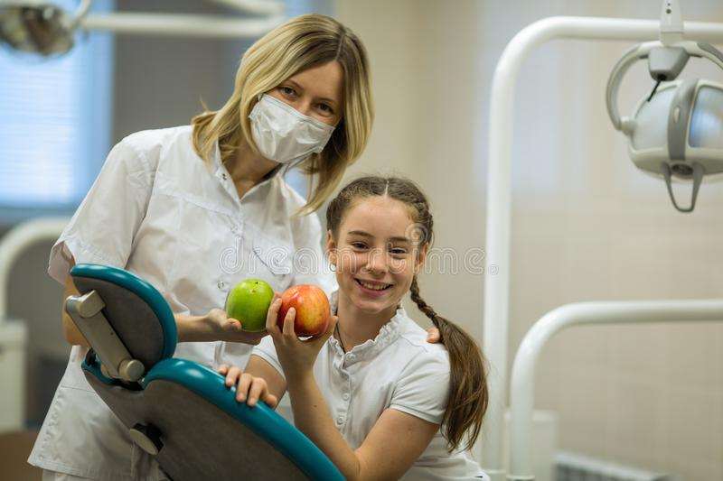 Female dentist gives apple for smiling teenage girl in modern clinic royalty free stock photo