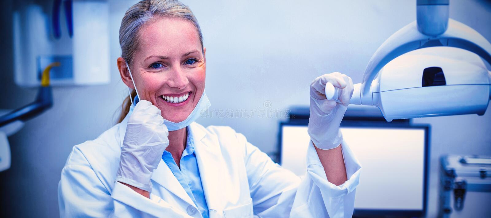 Female dentist holding dental lights. In dental clinic royalty free stock photography