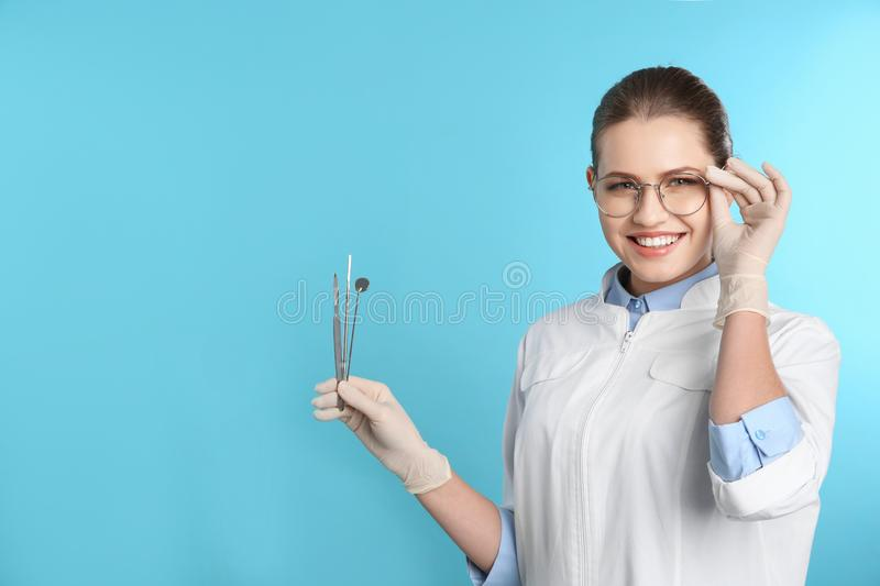 Female dentist holding professional tools on color background. Space for text stock image