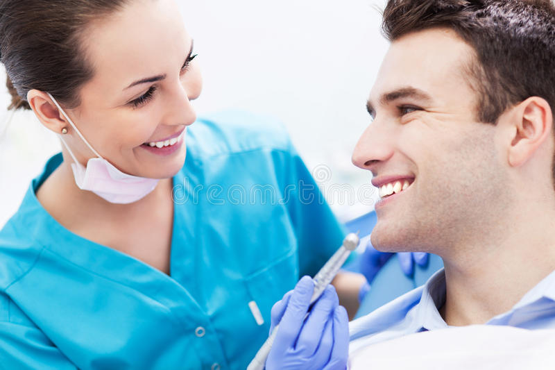 Female dentist with male patient. Female dentist and men in dentist's office stock photo