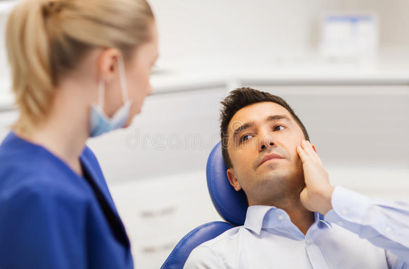 Female dentist and male patient with toothache. People, medicine, stomatology and health care concept - male patient with toothache complaining to female dentist royalty free stock photo