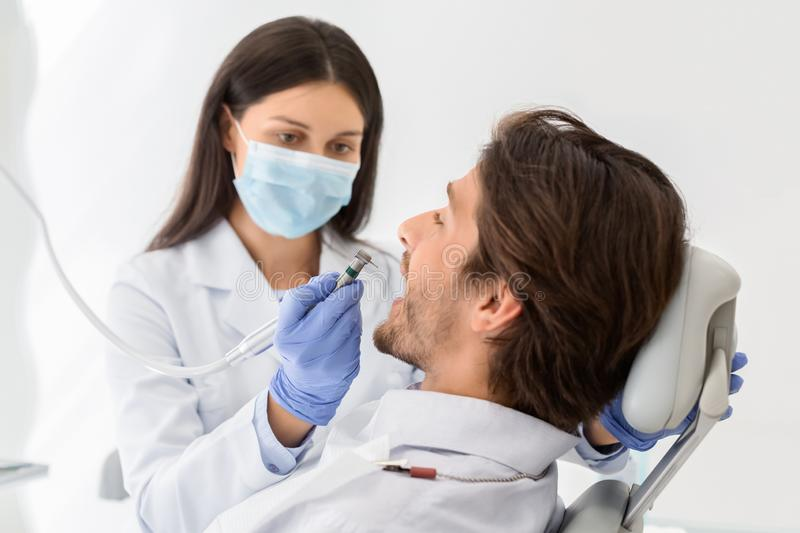 Female dentist in protective mask drilling male patient teeth royalty free stock images