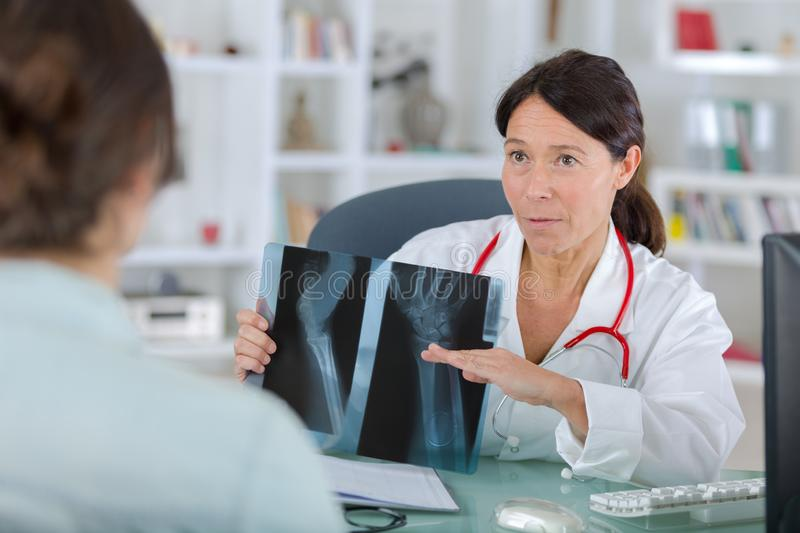 Female dentist showing x-rays to patient royalty free stock photography