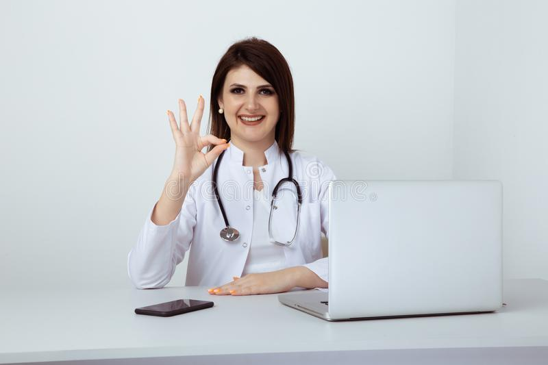 Female dentist in uniform sitting at the desk and working with dental staff in office. stock images