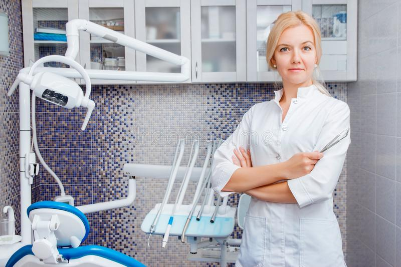 A female dentist in white uniform poses against a background of dental equipment in a dental office. Happy patient and dentist royalty free stock images