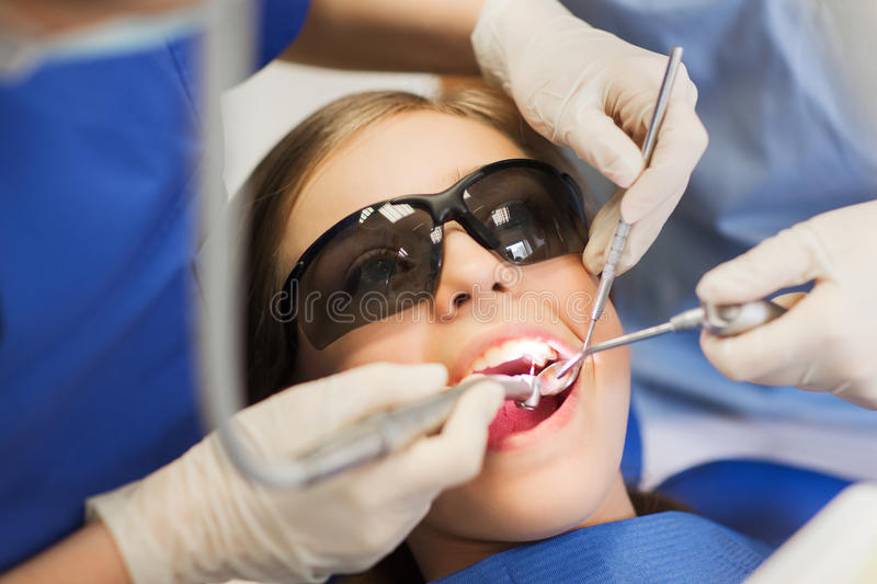 Female dentists treating patient girl teeth stock photo