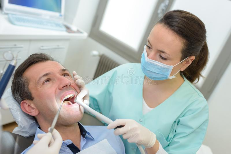 Female dentists working on young male patient royalty free stock photos