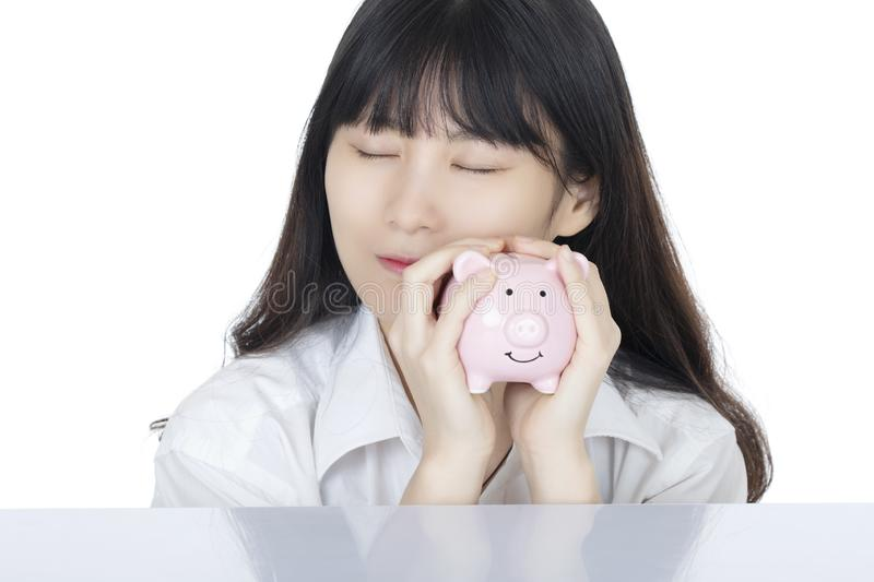 Female depositing American coins piggy bank isolated, white background. Female putting Amicana coins and placing a quarter into a piggy bank isolated on white royalty free stock photography