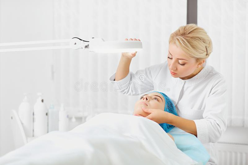 A female dermatologist examines the face of a girl. royalty free stock photo