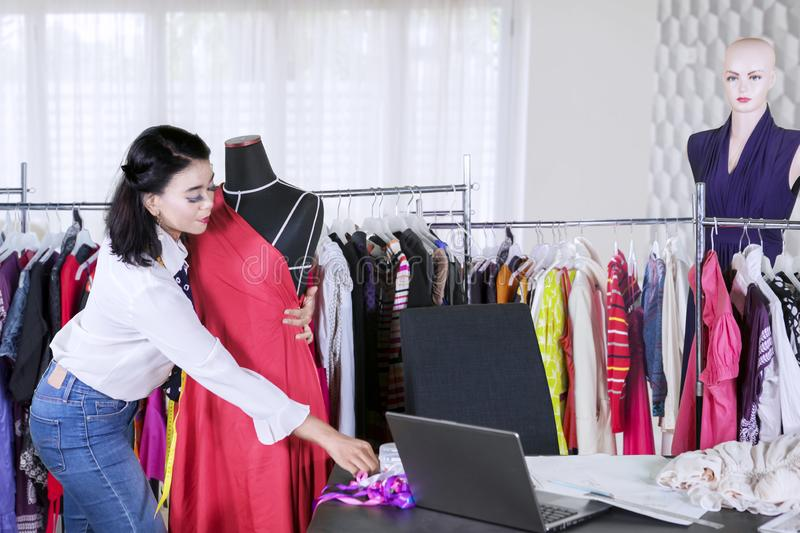 Female designer adjusts a dress on a mannequin royalty free stock photo
