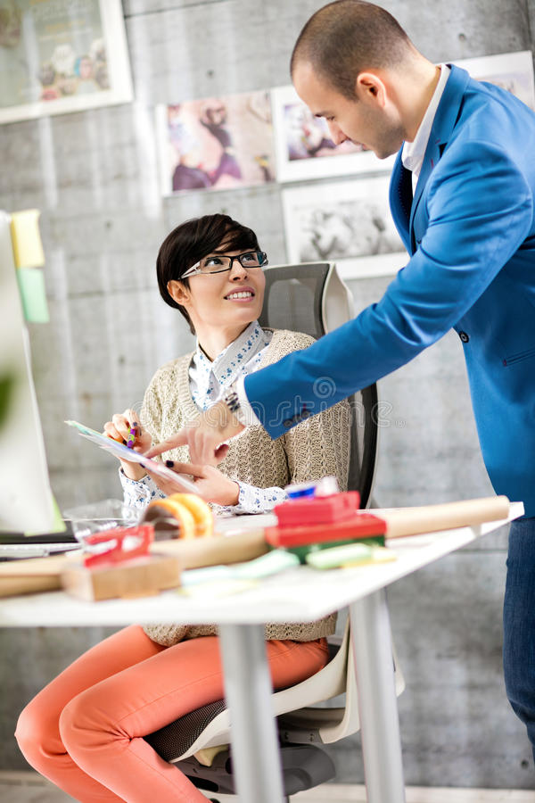 Female designer in consultation with supervisor. Young female designer in consultation with supervisor in design studio royalty free stock photography