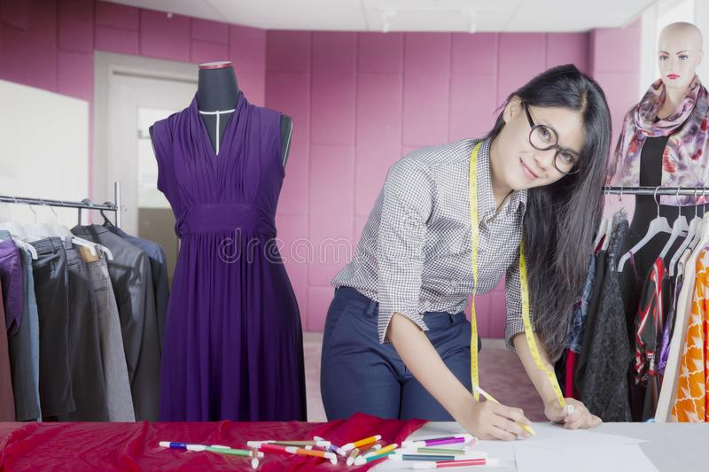 Female designer draws sketch in the office. Female fashion designer looks happy while drawing sketch for new dress and standing in the office stock images