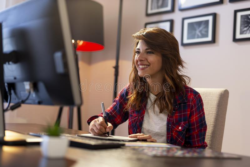 Female graphic designer using a drawing pad. Female designer holding a pen and drawing on a graphic board royalty free stock photo