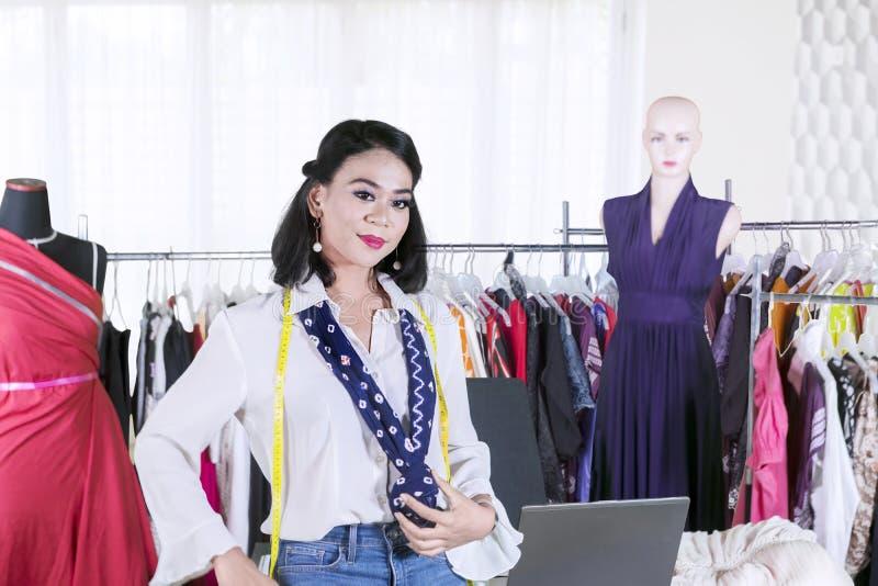 Female designer looks confident in the workplace. Picture of female fashion designer looks confident while standing in the workplace royalty free stock photography