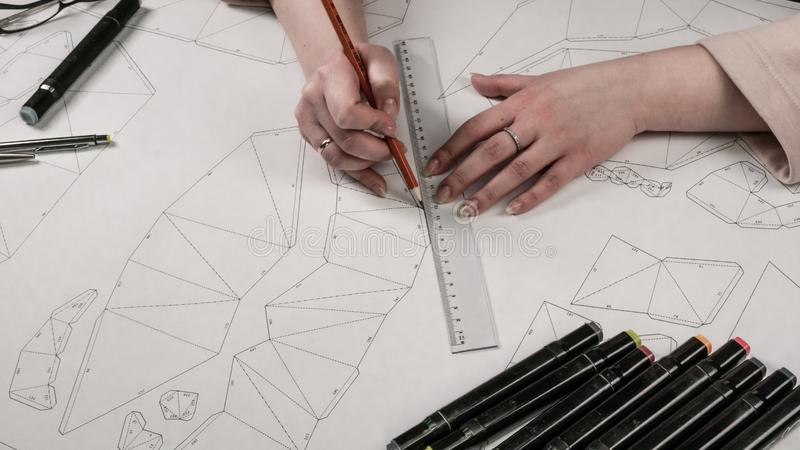 Female designer makes a working drawing. Workplace of a toy designer. Markers, ruler, pen and pencil are on the drawing stock images