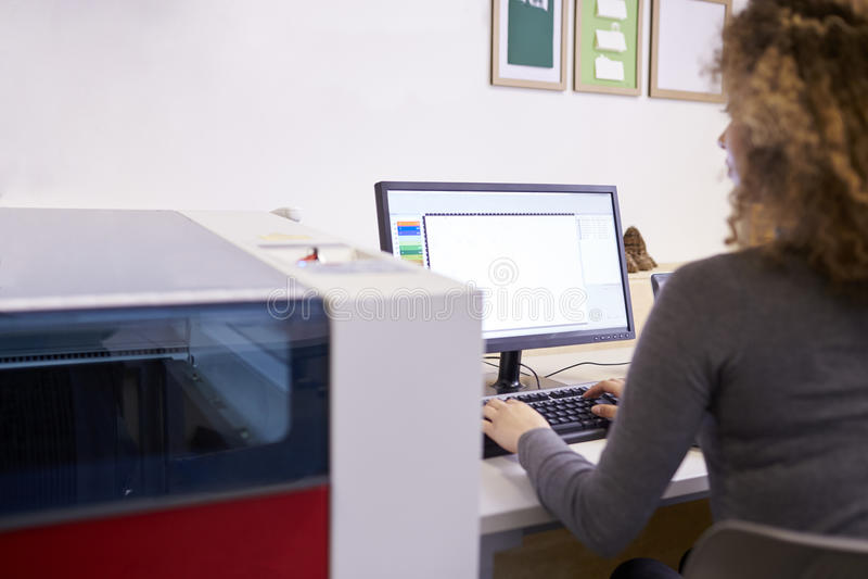 Female Designer Operating CAD System For Laser Cutter stock photo