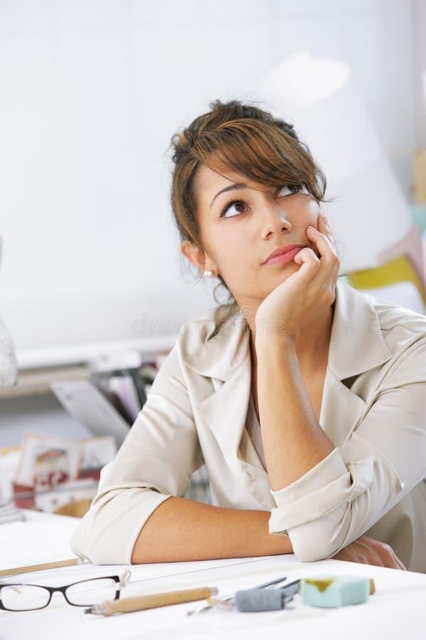 Female designer thinking. Portrait of attractive female designer royalty free stock image