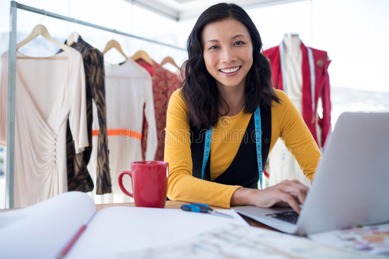 Female designer using laptop. In office royalty free stock image