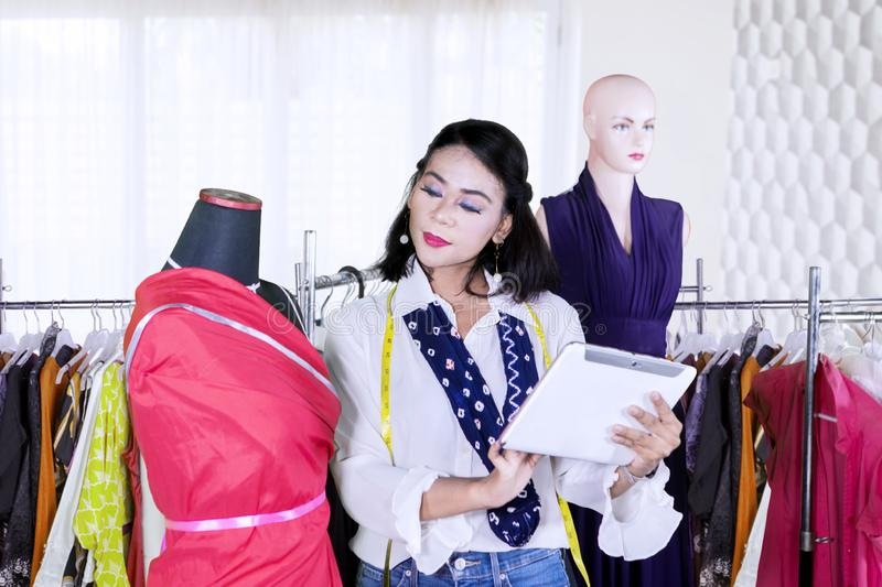 Female designer using a tablet in the workplace. Young female designer working with a mannequin while using a digital tablet in the workplace stock photo