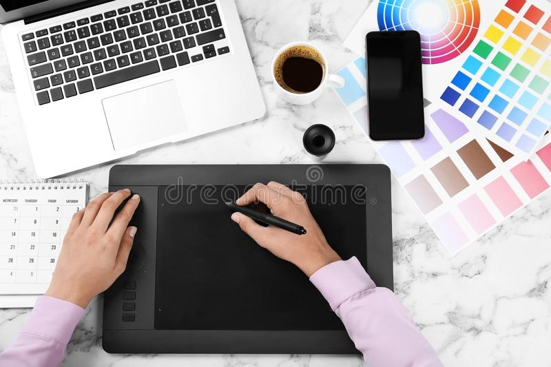 Female designer working with graphic tablet at white marble table. Top view stock photography