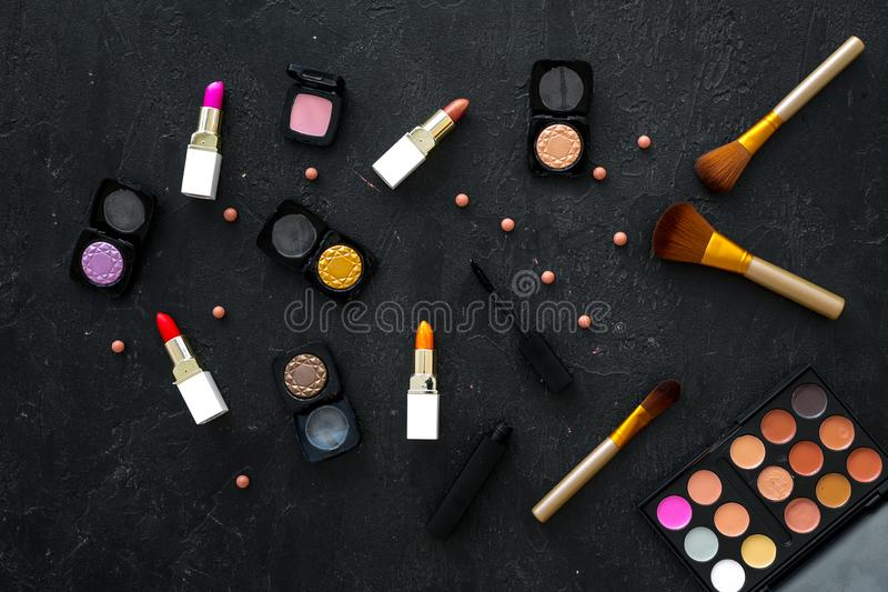 Female desk with decorative cosmetics for make up dark background top view pattern. Female desk with decorative cosmetics for make up on dark background top view royalty free stock photo