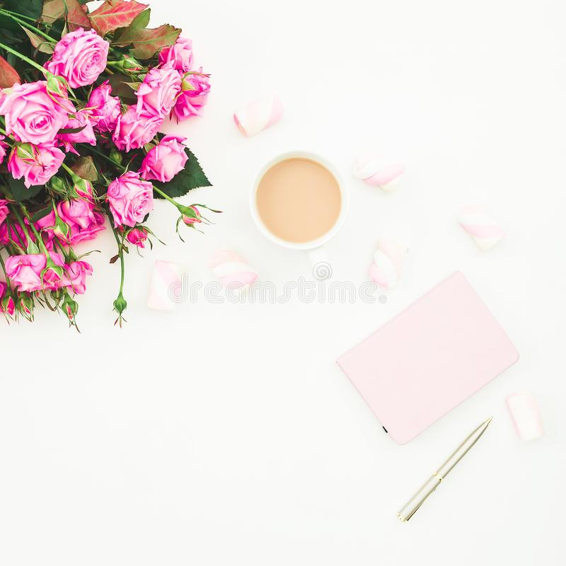 Female desk with pink roses bouquet, pink diary, coffee mug and marshmallows on white background. Flat lay. Top view feminine back stock images