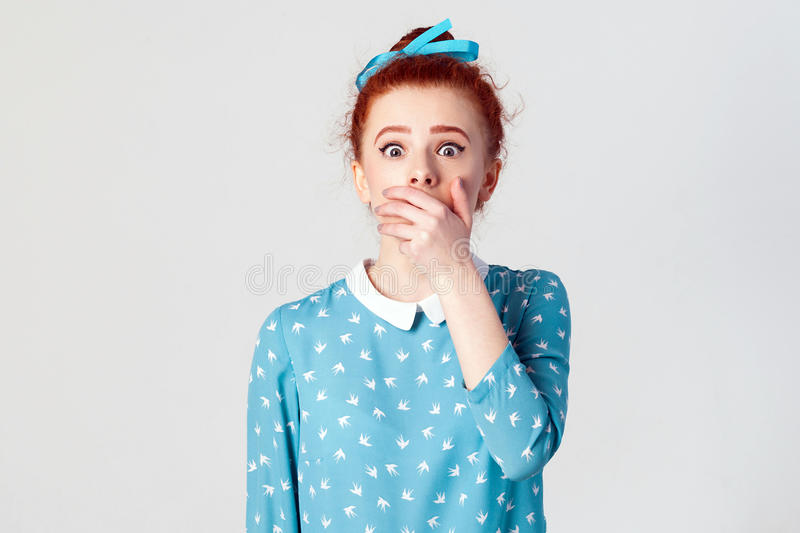 Female in despair and shock. Portrait of young desperate redhead girl in blue dress looking panic, covered her mouth by hand. stock photo