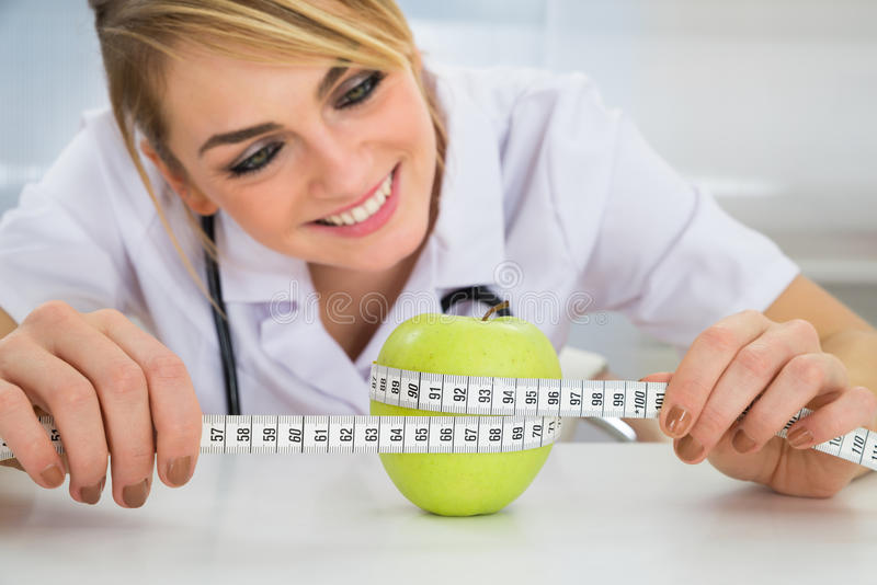 Female dietician measuring green apple royalty free stock photography