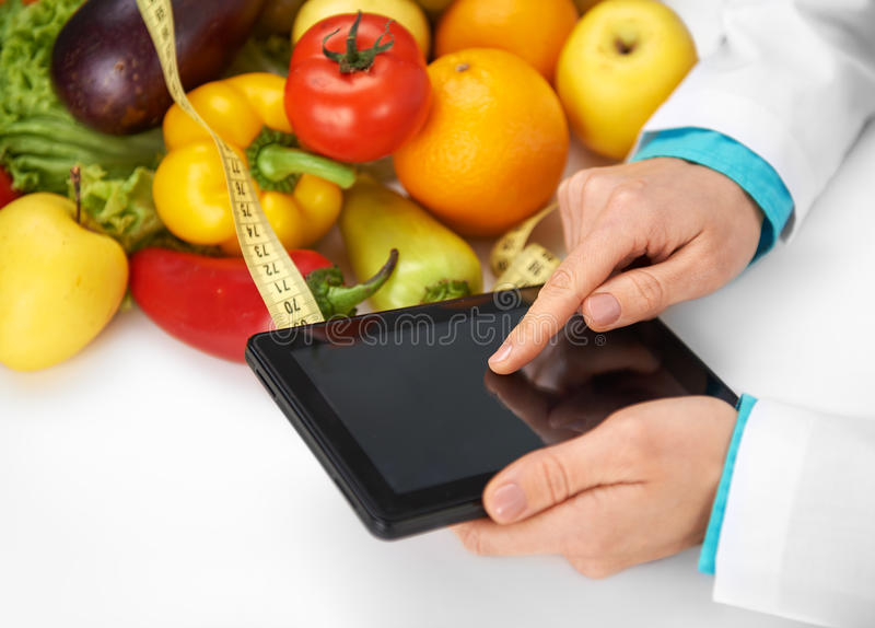 Female Dietitian. Close-up of female dietitian hands holding tablet pc in her office. Concept of diet, medicine and technology royalty free stock images