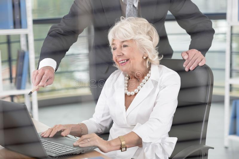 Female director in office. Mature female director in office working on laptop royalty free stock photo