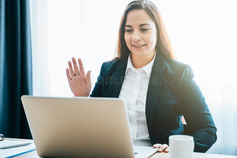 Female distant teacher or friend making video call and talking, looking at laptop webcam, online chat or business stock photo
