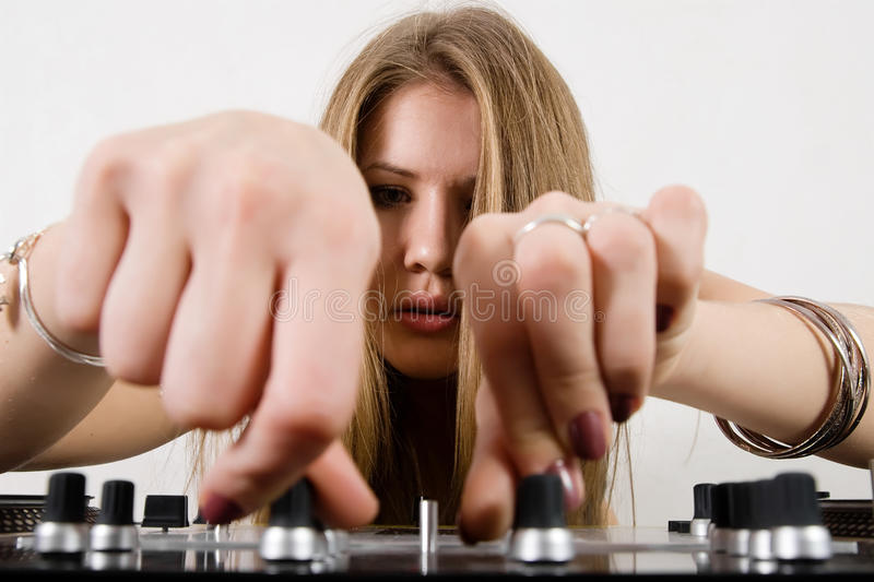 Female DJ adjusting sound levels. Blond girl with beautiful long hair playing music stock photo