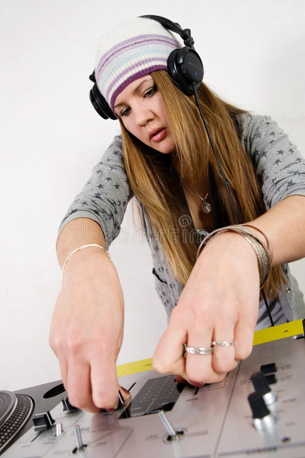 Female DJ adjusting sound levels. Young girl mixing music on professional mixing controller device royalty free stock images