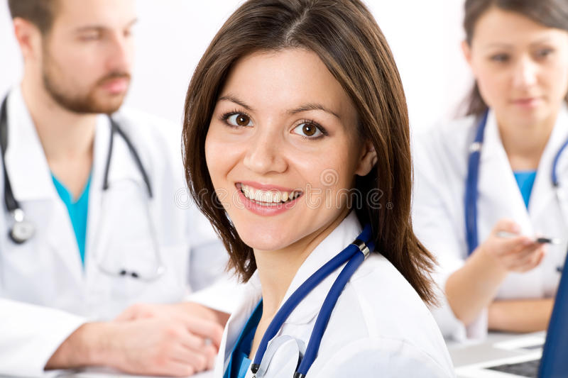Female doctor. The young female doctor and its colleagues stock images