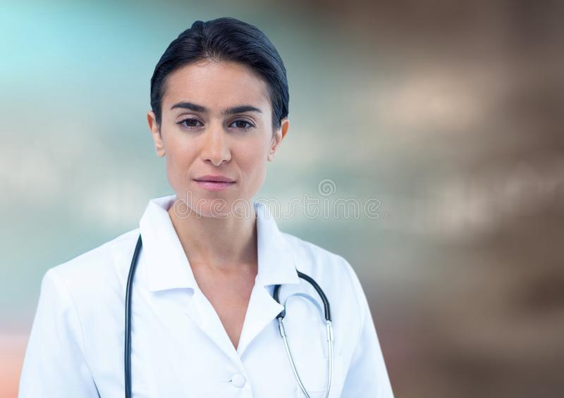 Female doctor against blurry blue brown background stock photo