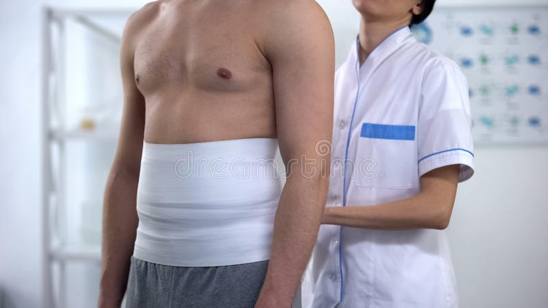 Female doctor applying back wrap male patient to decrease hypoxic tissue injury royalty free stock images