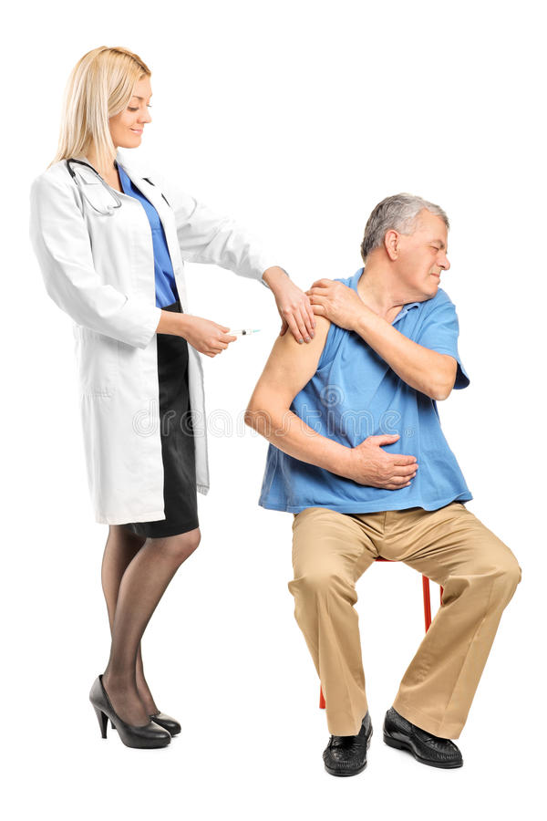 Female doctor applying a syringe to an elderly man stock photo