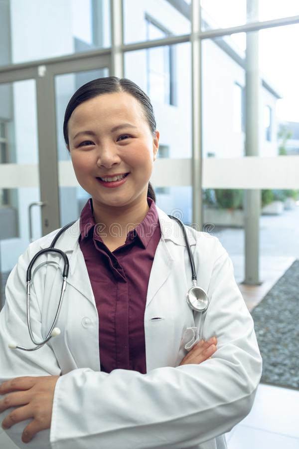 Female doctor with arm crossed looking at camera in the lobby of hospital stock photos