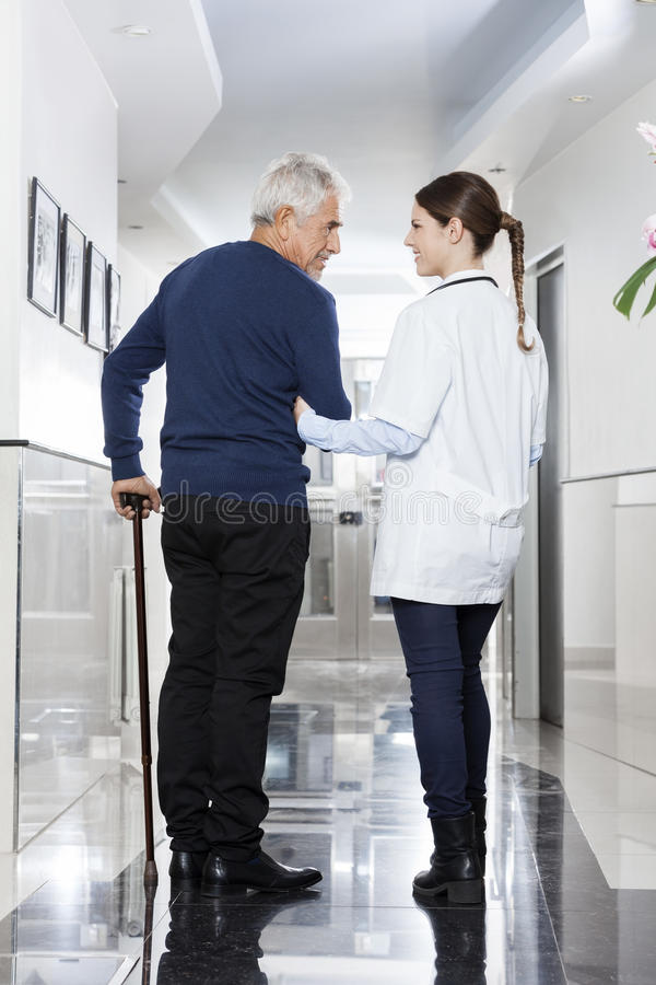 Female Doctor Assisting Man To Walk In Rehab Center stock photography