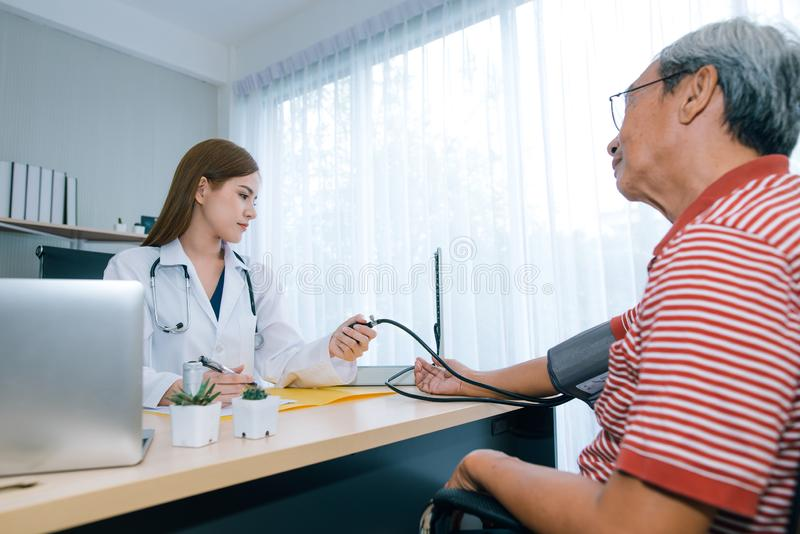 Female doctor checking blood pressure ff senior man patient. stock photo